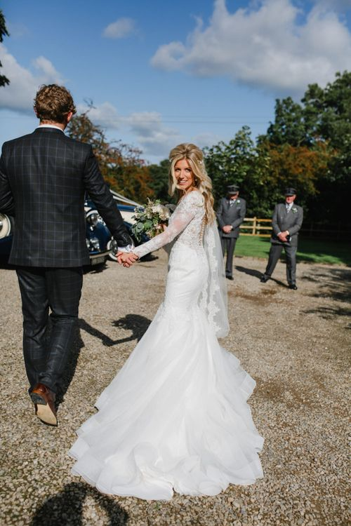 Bride in Lace Fishtail Nicole Spose Wedding Dress and Groom in Blue Check Most Suitable Suit  Holding Hands