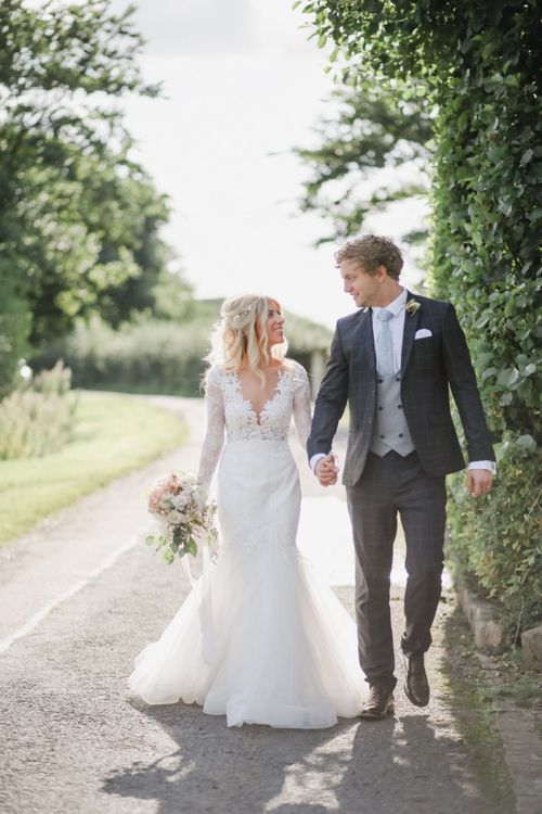 Bride in Lace Fishtail Nicole Spose Wedding Dress and Groom in Blue Check Most Suitable Suit Holding Hands Down a Country Lane