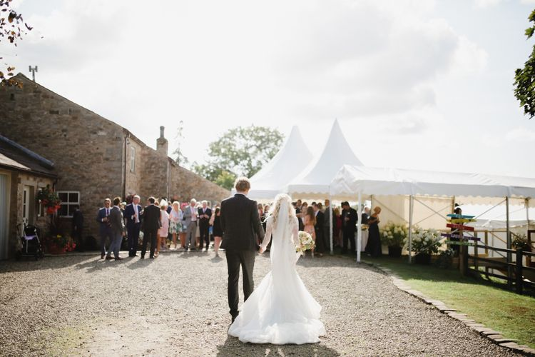 Bride in Lace Fishtail Nicole Spose Wedding Dress and Groom in Blue Check Most Suitable Suit Walking Towards Their Marquee Reception