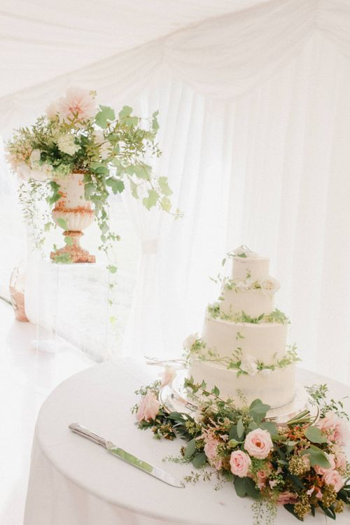 Wedding Cake Table with White Wedding Cake Decorated in Wedding Flowers
