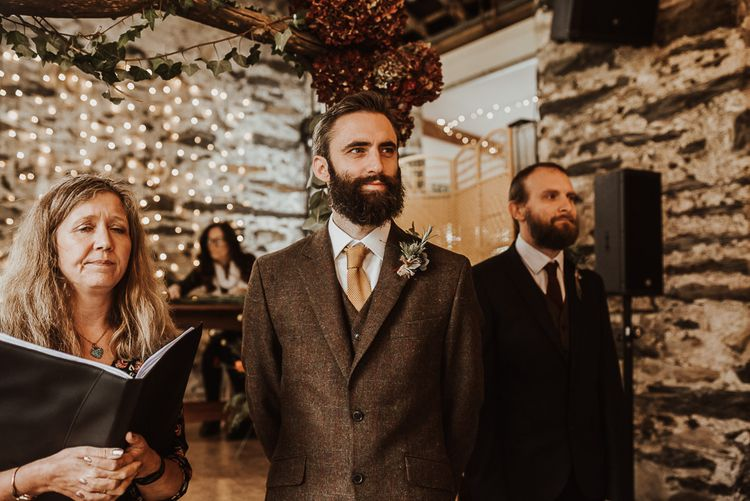Groom in brown suit waits for bride at ceremony