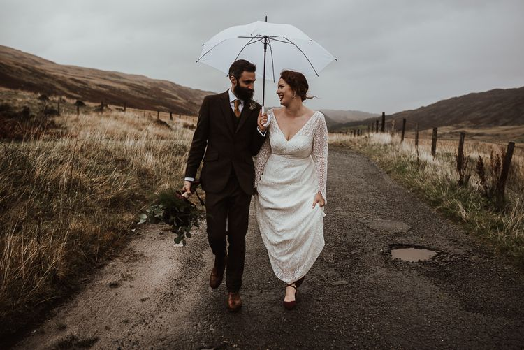 Bride and groom take a stroll in rain at Snowdonia wedding