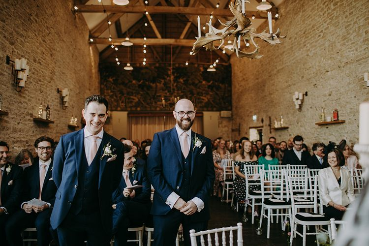 Groom and Best Man at the Altar in Navy Blue Moss Bros. Suits with Pink Ties
