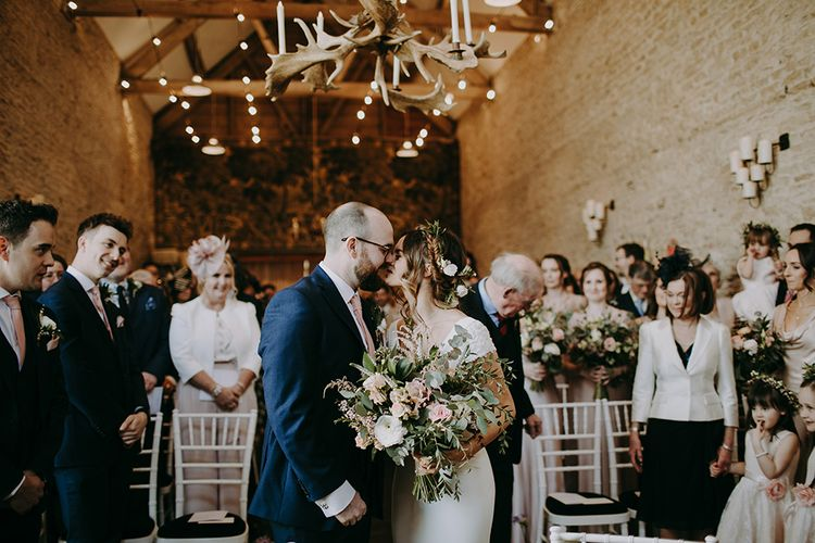 Bride in Pronovias Dralan Wedding Dress  and Groom in Navy Blue Moss Bros. Suit Kissing at the Altar