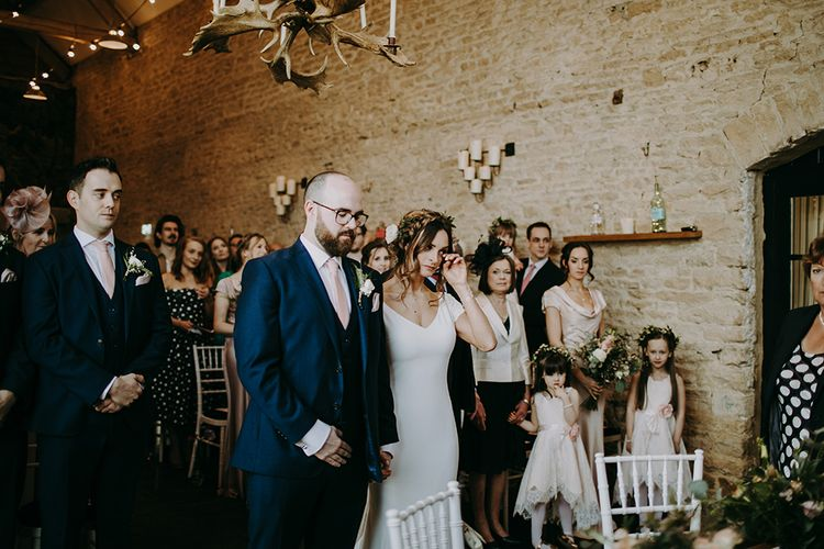 Emotional Bride in Pronovias Dralan Wedding Dress  and Groom in Navy Blue Moss Bros. Suit Standing at the Altar