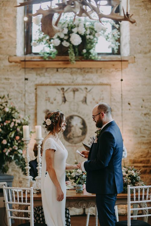 Bride in Pronovias Dralan Wedding Dress  and Groom in Navy Blue Moss Bros.  Suit Exchanging Vows During Wedding Ceremony