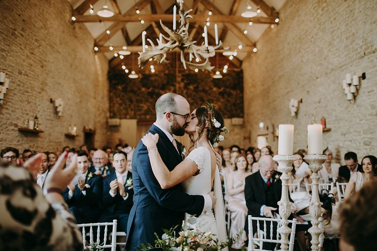 Bride in Pronovias Dralan Wedding Dress  and Groom in Navy Blue Moss Bros.  Suit Kissing During Wedding Ceremony