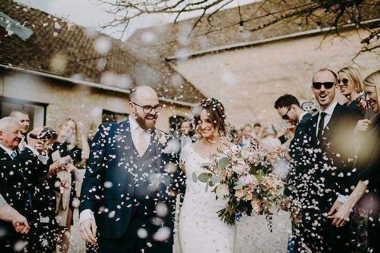 Confetti Moment with Bride in Pronovias Dralan Wedding Dress  and Groom in Navy Blue Moss Bros.  Suit