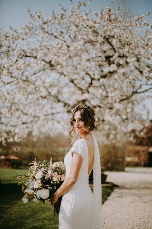 Bride in Pronovias Dralan Wedding Dress Standing in Front of White Blossom Tree