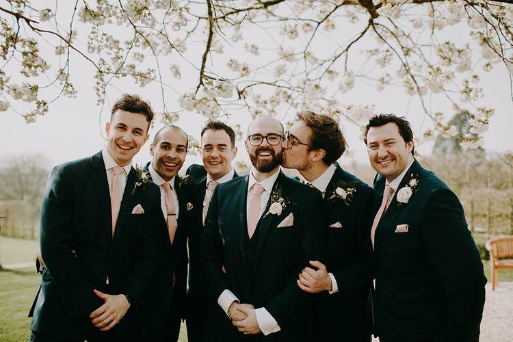 Groom and Groomsmen in Navy Moss Bros. Suitswith Pink Ties