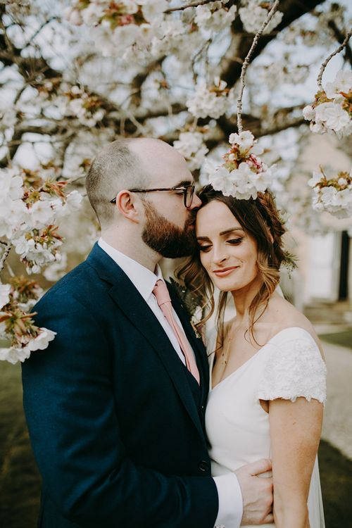 Bride in Pronovias Dralan Wedding Dress and Groom in Navy Moss Bros. Suit with Pink Tie Standing in Front of a Blossom Tree