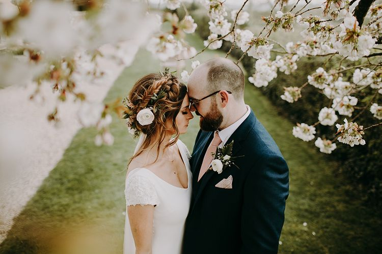 Bride in Pronovias Dralan Wedding Dress and Groom in Navy Moss Bros. Suit Cuddling in Front of a Blossom Tree