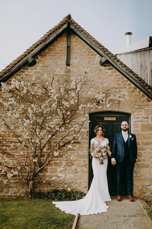 Bride in Pronovias Dralan Wedding Dress and Groom in Navy Moss Bros. Suit