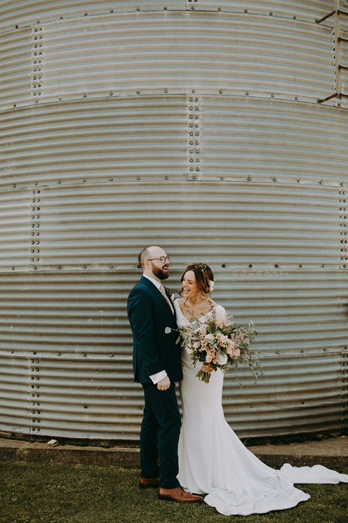Bride in Pronovias Dralan Wedding Dress and Groom in Navy Moss Bros. Suit Laughing