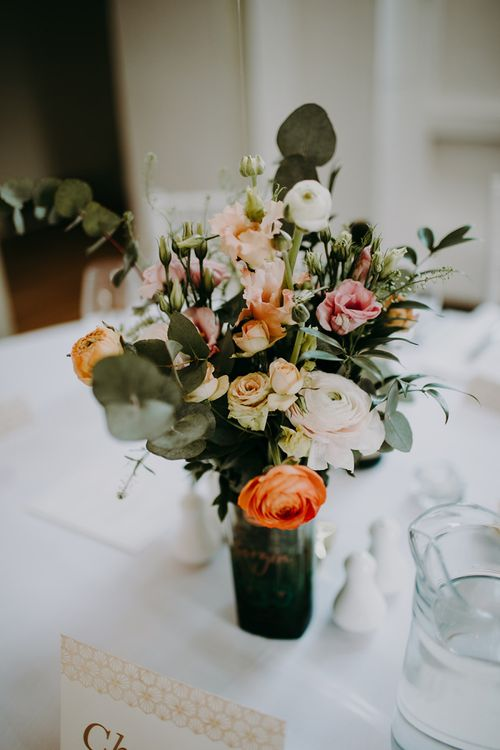 Wedding Floral Arrangements in Gin Bottles as Table Centrepieces