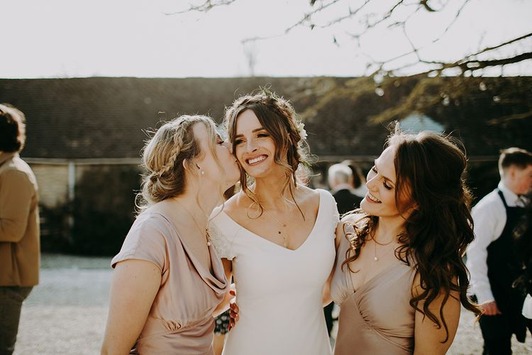 Bridesmaid in Pink Ghost Dress Giving Bride in Pronovias Dralan Wedding Dress a Kiss