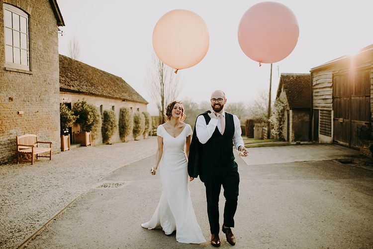 Bride in Pronovias Dralan Wedding Dress and Groom in Navy Moss Bros. Suit Holding Giant Pink and Peach Balloons