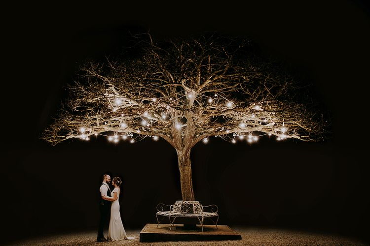 Bride in Pronovias Dralan Wedding Dress and Groom in Moss Bros. Suit Standing by a Fairy Light Covered Tree