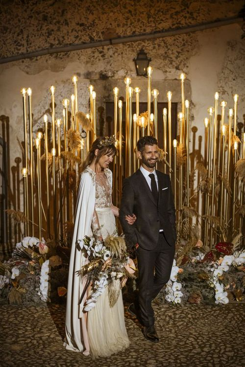 Stylish Bride and Groom Standing in Front of Gold Wedding Lighting
