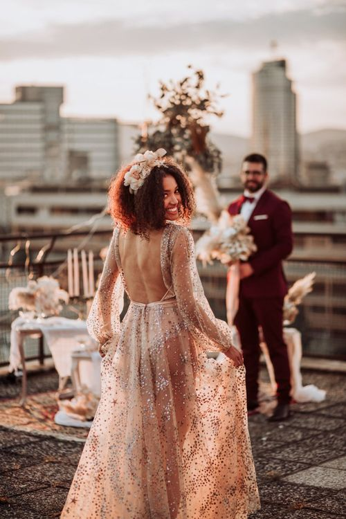 Bride in backless sparkle wedding dress with flowers in her hair