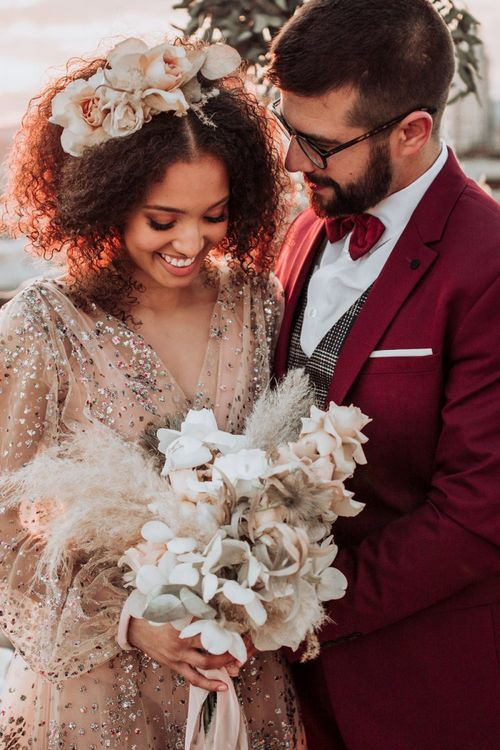 Bride in sparkle wedding dress holding a orchid and pampas grass bouquet