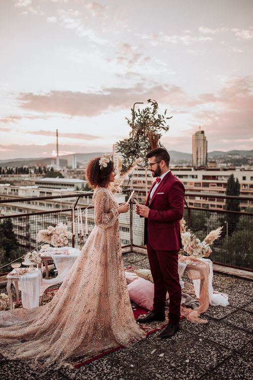 Bride and groom exchanging vows on a rooftop in sparkle wedding dress and burgundy suit