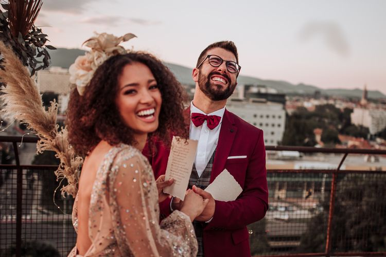 Groom in red suit and bow tie laughing during intimate wedding ceremony