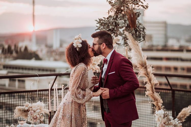 Bride and groom kissing at rooftop wedding