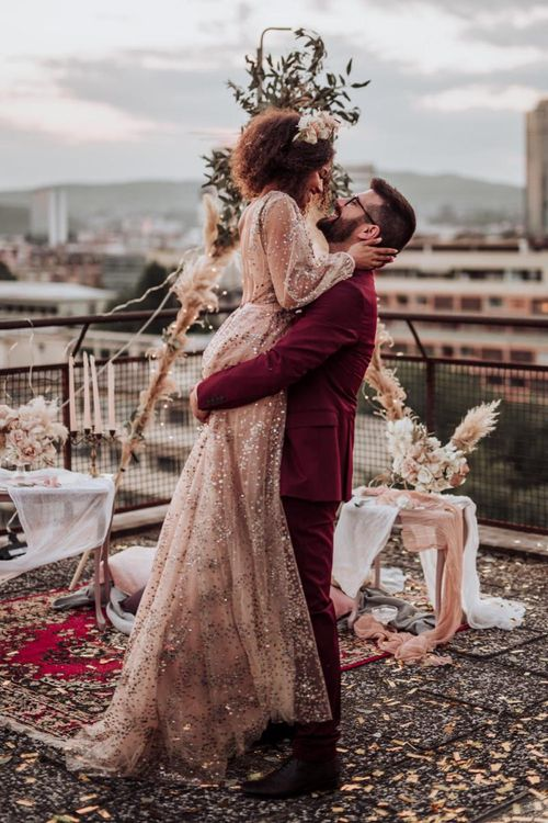Bride in sparkle wedding dress and groom in burgundy suit at intimate boho wedding