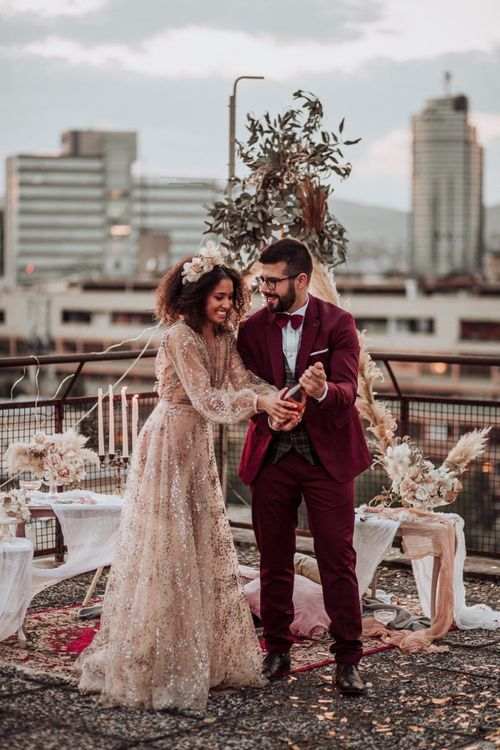 Bride in sparkle wedding dress and groom in burgundy suit popping champagne at rooftop wedding