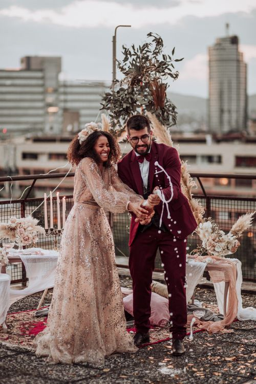 Bride in sparkle wedding dress and groom in burgundy suit popping champagne