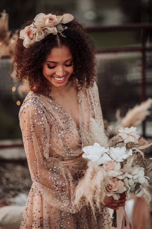 Boho bride in sparkle wedding dress with long sleeves and flowers in her curly hair