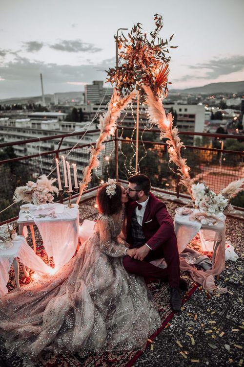 Bride in sparkle wedding dress kissing her groom