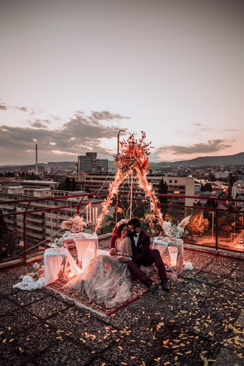Intimate rooftop wedding celebration with fairy light covered tipi structure