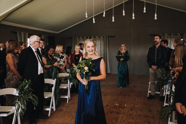 Bridesmaid Walks Down The Aisle For Wedding With Polaroid Guest Book
