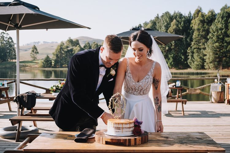 Bride and Groom Cut The Wedding Cake With Cake Topper