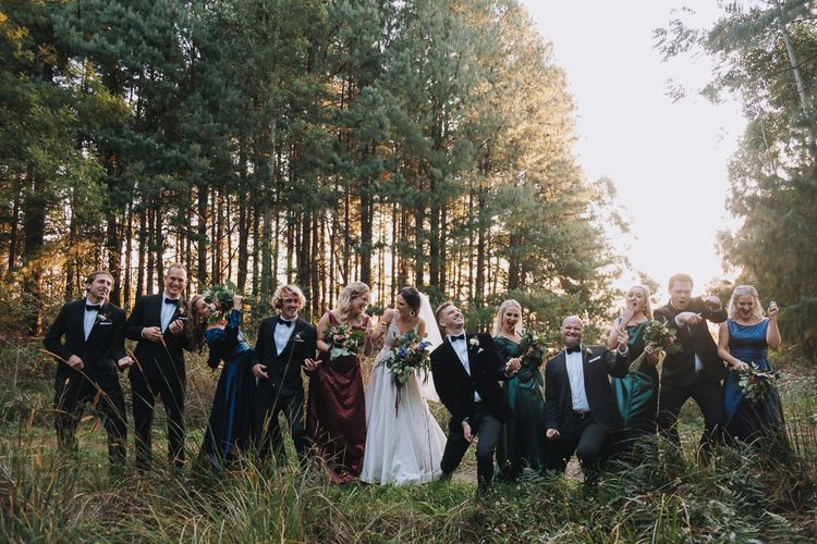 Wedding Party Strikes A Pose In Forest At Cool Wedding With Polaroid Guest Book