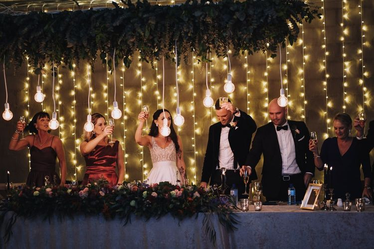 Happy Couple And Guests Toast During Wedding Speeches In Front Of Fairy Lights