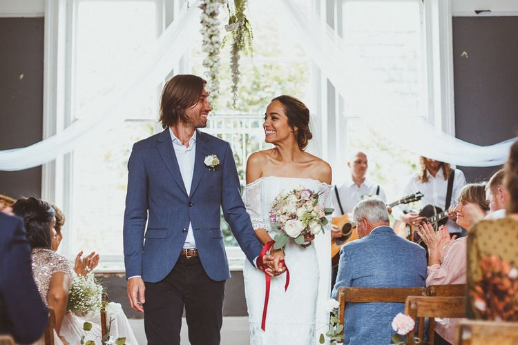 Happy Bride and Groom Just Married with Bride in 'Emanuela' Grace Loves Lace Wedding Dress and Groom in Black Trousers, White Shirt and Blue Blazer
