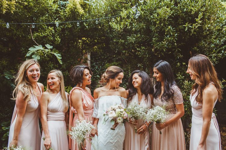 Bridal Party Looking at Gypsophila Bouquets with Bride in Grace Loves Lace Wedding Dress