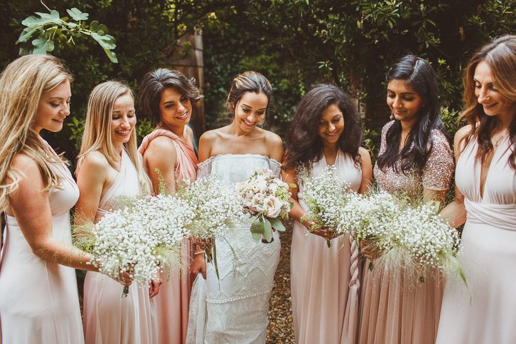 Bridal Party Portrait with Bride in Grace Loves Lace Wedding Dress and Bridesmaids in Different Blush Dresses
