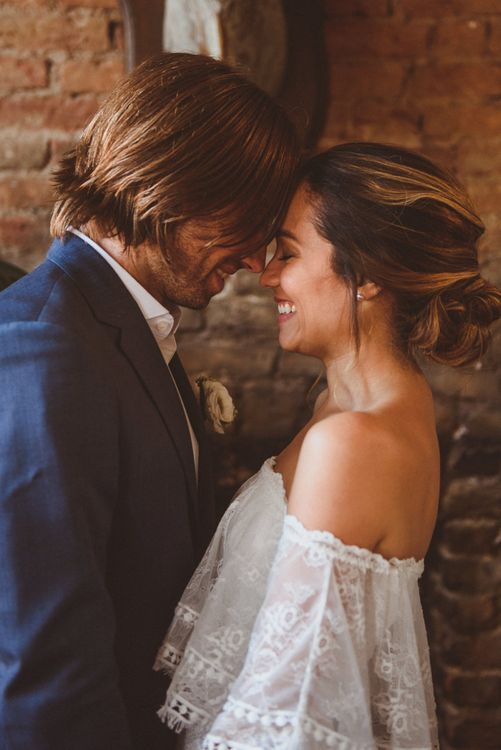 Bride in Grace Loves Lace Dress and Groom in Blue Blazer Embracing