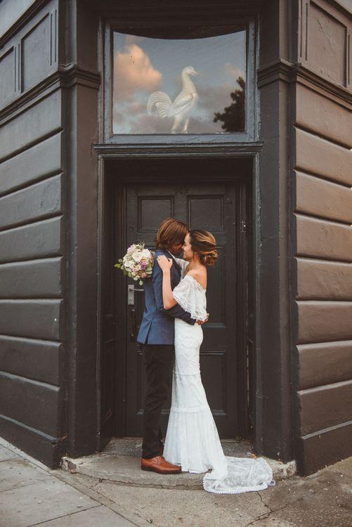 Bride in Off The Shoulder Grace Loves Lace Wedding Dress and Groom in Blue Blazer Cuddling