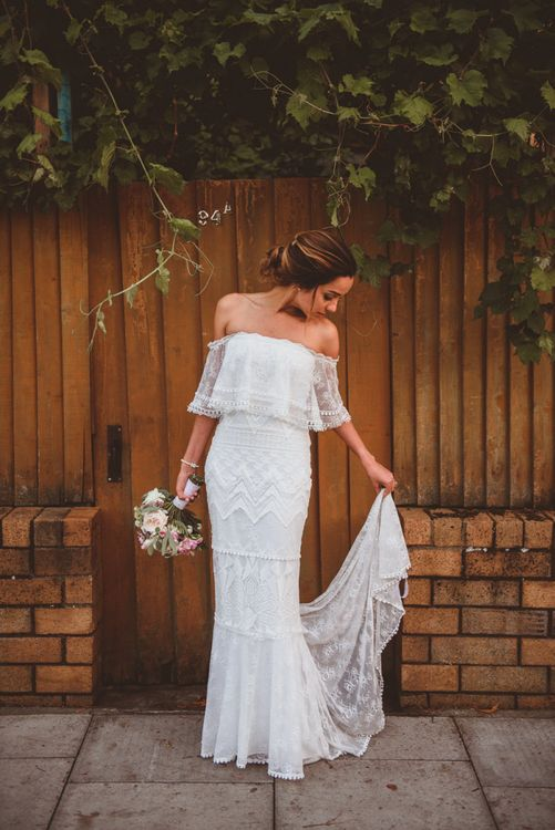 Beautiful Bride in Off The Shoulder 'Emanuela' Grace Loves Lace Wedding Dress Holding Her Train & Bouquet