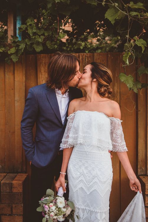 Bride in Off The Shoulder Grace Loves Lace Wedding Dress and Groom in Blue Blazer Kissing