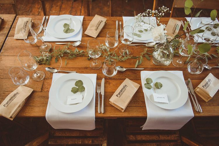 Wooden Table with White Tableware and Foliage Decor