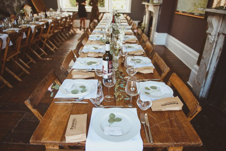 Reception with Wooden Tables, White Tableware and Foliage Decor