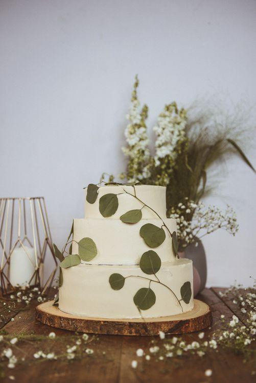 White Buttercream Cake on Tree Slice Cake Stand with Foliage Decor