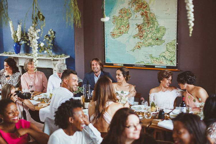 Bride and Groom Sitting at the Top Table with Giant Map Backdrop