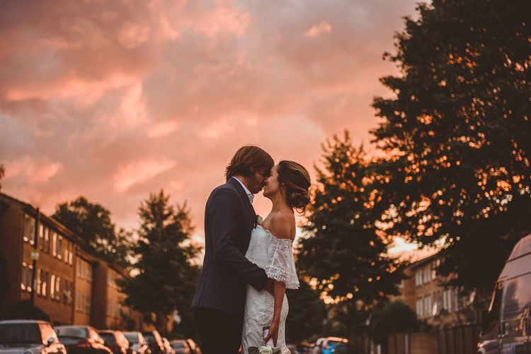 Bride in Off The Shoulder Grace Loves Lace Dress and Groom in Blue Blazer Kissing During Golden Hour